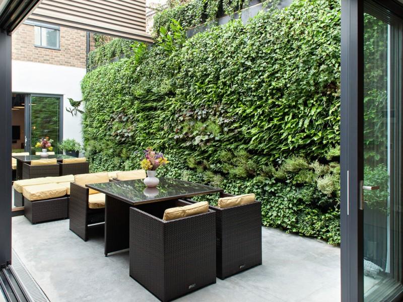 vertical garden plans rattan chairs benches glasstop table concrete slab screen panels glass door climbing vines brick walls contemporary design