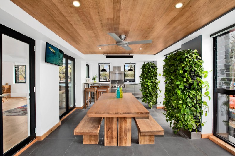 vertical garden plans wood narrow table benches chairs kitchenette stainless steel appliances cabinets grey walls double glass doors fans ceiling lights contemporary design