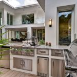 viking outdoor kitchen stainless steel appliances fridge wooden tile wall lamps utensils cabinets countertop island contemporary style