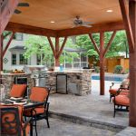 viking outdoor kitchen stone tile chairs table pool stainless steel appliances drawers cabinets countertop ceiling fan light traditional style