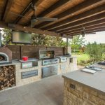 viking outdoor kitchen wooden ceiling fireplace tv countertop faucet oven fridge appliances stainless steel cabinets fan traditional style