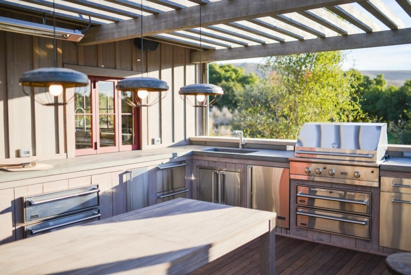 viking outdoor kitchen wooden floor long table stainless steel appliances stove oven cabinets drawers hanging lamps window glass ceiling farmhouse style