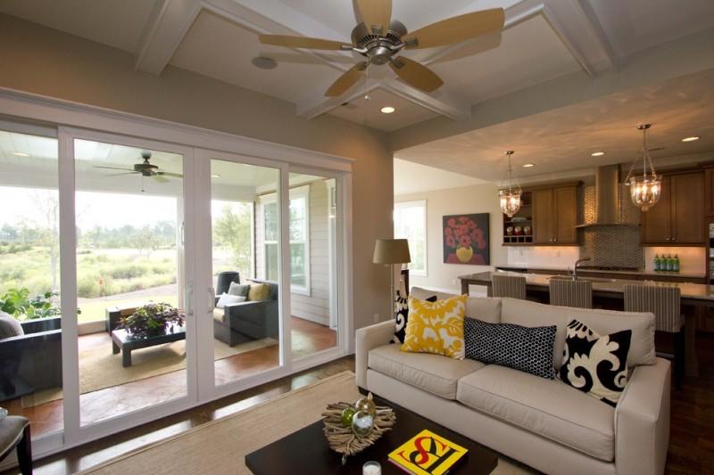 white pottery barn sofa coffee table cream rug ceiling fan pillow throws medium toned wooden floor cream walls