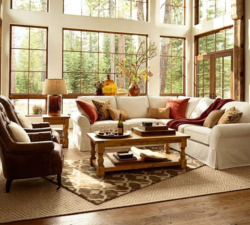 white soffa brown sofa chairs cream rug diagonal rug pillow throws white walls big glass window table lamp vases wooden deck floor