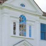 White Wooden Colonial Front Door With Beautiful Detailed Portico With Glasses On Top Of The Door