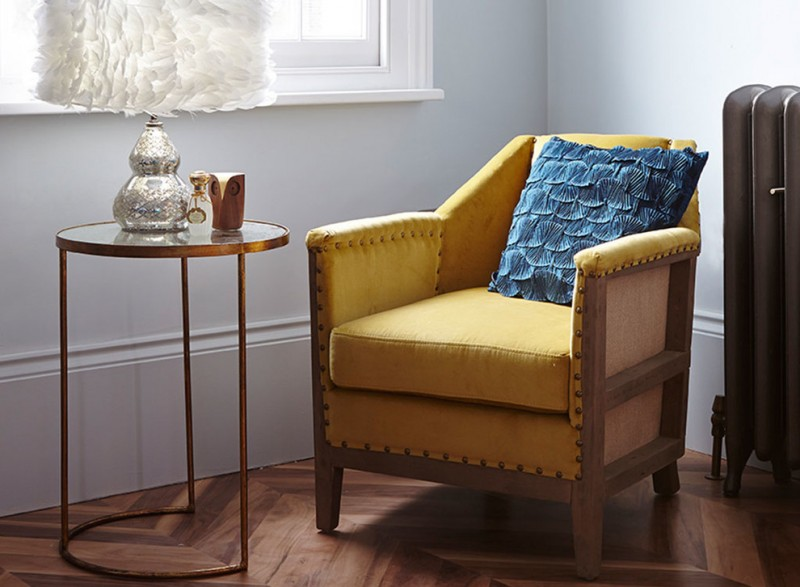 wood chair with yellow seater and blue decorative pillow medium toned wood floorings with symmetrical patterns white walls round top glass side table with copper base