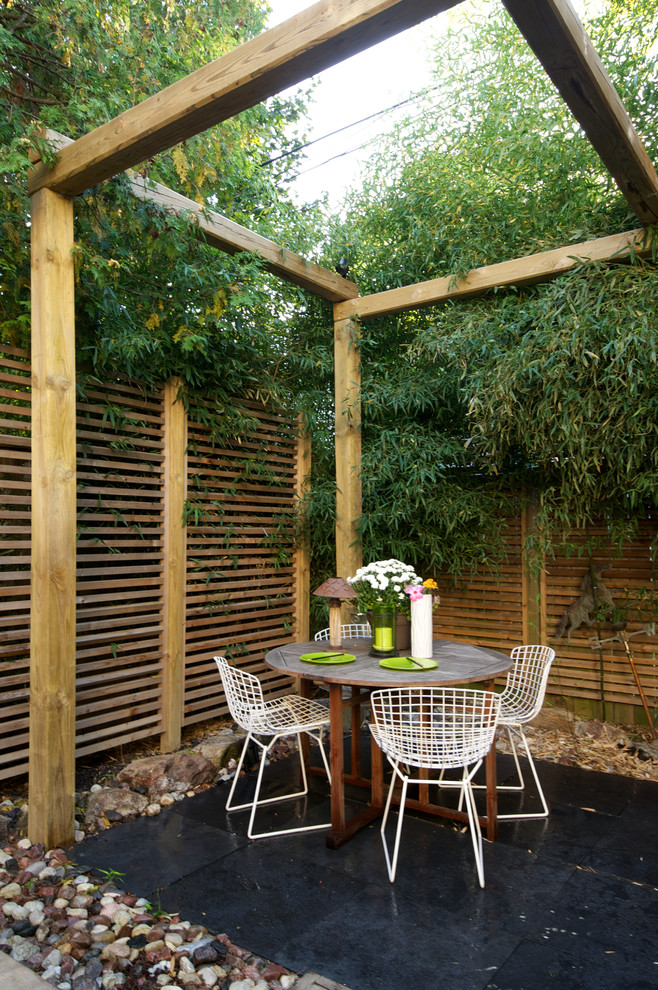 Asian fusion patio idea with simple logs pergola supported by privacy fence white and light metal chairs round shape wood table black ceramic tiles floors stones landscaping idea
