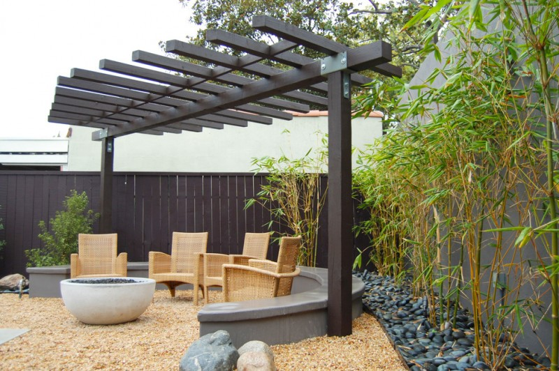 Asian patio idea with single row pergola in black rattan chairs gravel floors black painted privacy fence decorative bamboos
