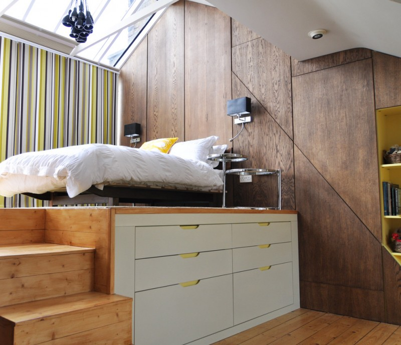 Contemporary bedroom with white painted storage drawers underneath loft bed wooden stairs walls and floors