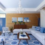 L Shaped White Sofa Blue Accent Chairs And Rug Wooden Coffee Table And Cabinet Deck Wooden Wall Chandelier Lamp Medium Toned Wooden Floor