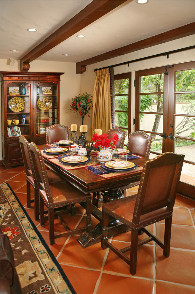 Mediterrenean dining room with dark hardwood dining furniture dark hardwood corner cabinet with transparent glass door terracotta tiles floors white ceilings white walls
