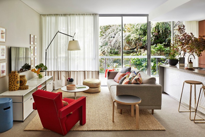 Mid sized contemporary open concept family room with carpet, a wall mounted tv and beige walls red accent chair free standing lamp bar stools white cabinet