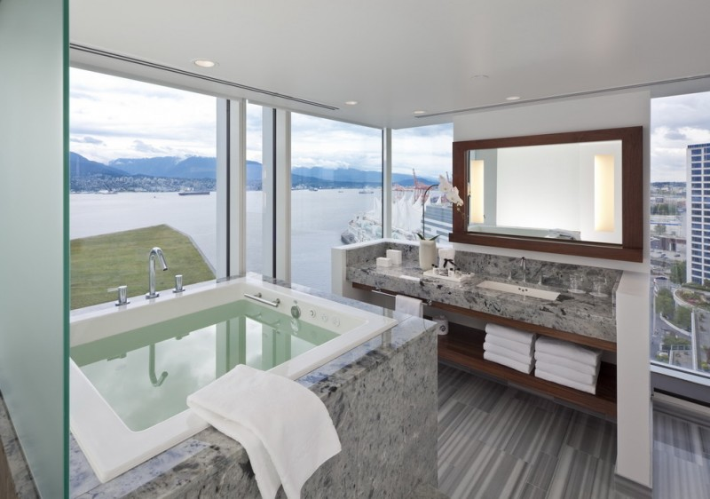 Mid sized trendy master bathroom with an undermount sink open cabinets dark wood cabinets a drop in tub gray tile a two piece toilet white wall, porcelain floors and granite countertops