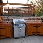 Mission Style Bakcyard Patio And Outdoor Kitchen Wooden Cabinets With Wood Countertop Stainless Steel BBC Cooker Mexican Tiles Backsplash