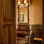 Mission Style Bathroom Idea Recycled Oak Vanity Metal Framed Mirror Warm & Yellow Light Lamps Beige Concrete Walls