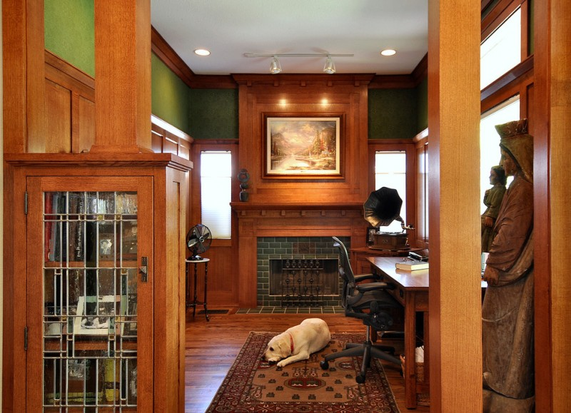 Mission Style home office with wood mantled fireplace accented by green tiles surface dark toned wood floors dark hardwood wainscoting wooden working desk black working chair traditional area rug
