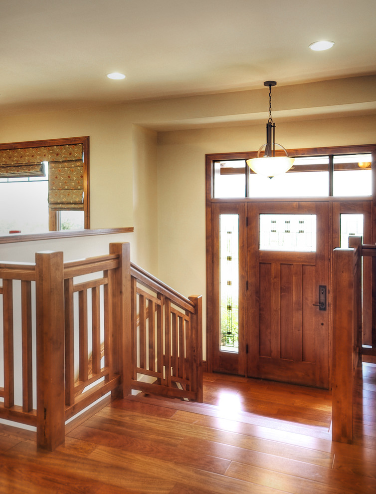 Mission style hallway idea with craftsman front door wooden stair railing system and wooden floors