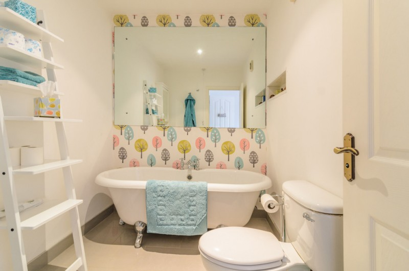 Small trendy bathroom with ladder shelf claw foot tub and multicolored walls a large mirror brown tile ceramic floor