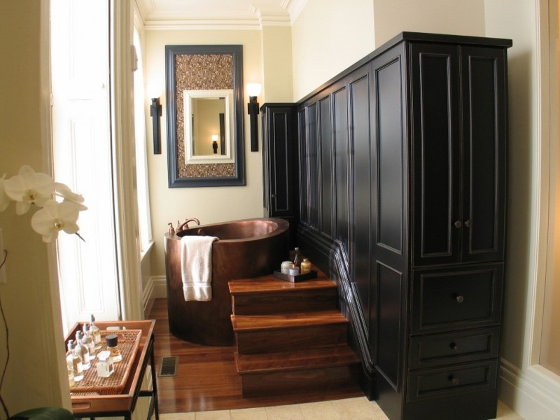 Traditional bathroom idea with a Japanese tub black painted custom cabinets medium toned wooden floors and stairs lamp sconces mirror