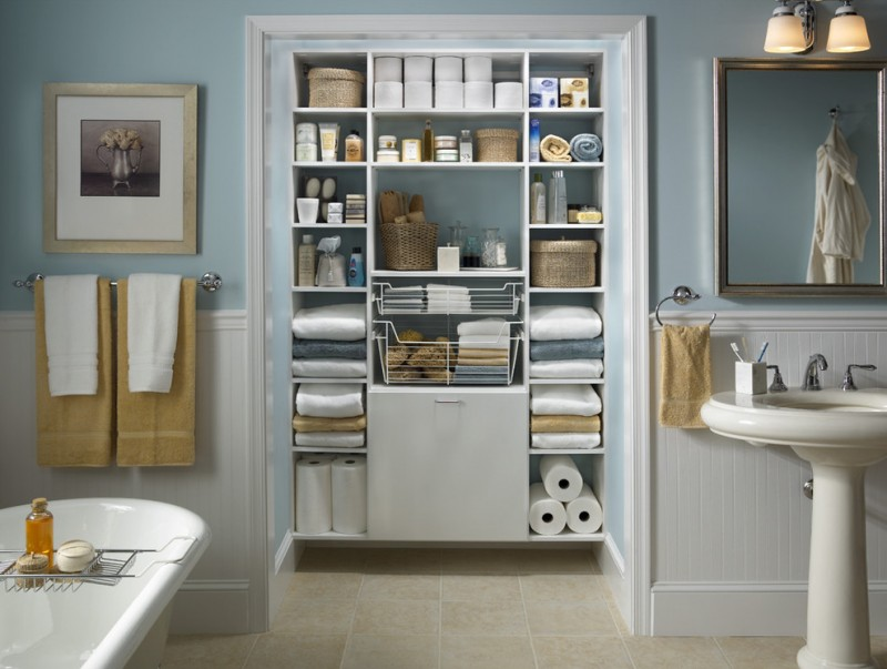 Traditional bathroom with walk in closet open shelves a freestanding tub and a pedestal sink rectangular mirror blue and white wall
