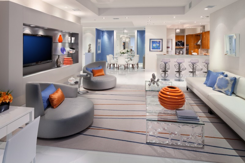 Trendy family room with white walls a wall mounted tv and white floors blue pillows on the round sofas yellow orange and red orange vase glass table a red orange sculpture multi color carpet