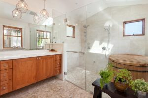 Tuscan master walk in shower with shaker cabinets medium tone wood cabinets white wall, pebble tile floors a trough sink and gray tile