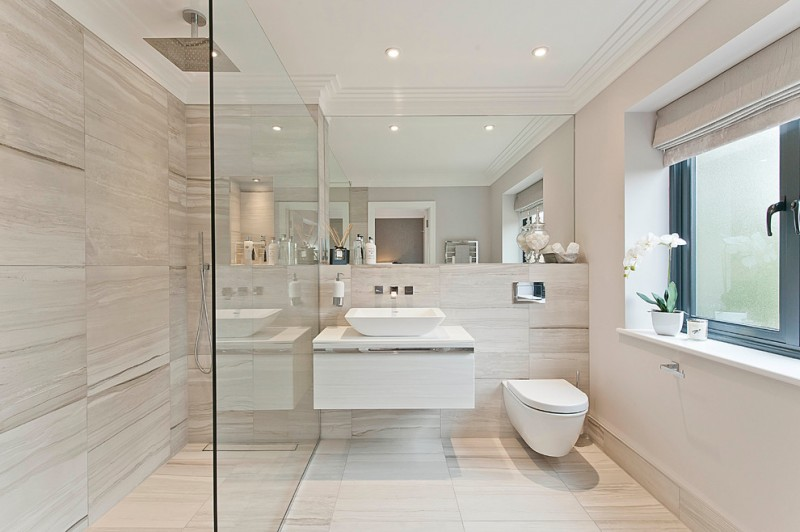 Wall hung toilets with tanks behind the wall floating sink glass door shower room white wall and ceiling brown tile ceramic bathroom floor and wall