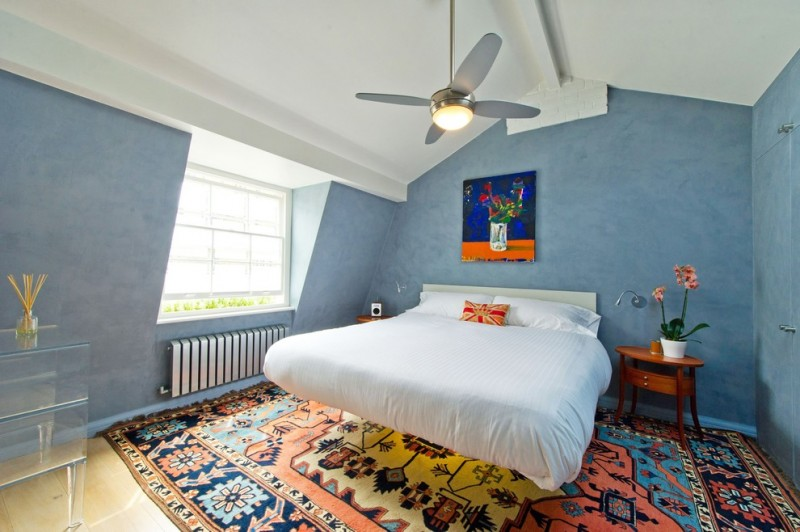 airy and light bedroom with white bedding idea dark finished wood bedside tables multicolored area rug blue walls white ceilings handmade painting