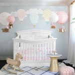baby girl bedroom theme crib white cabinet lamp hot air balloon decoration plant pot horse toy sidetable pouffe transitional design