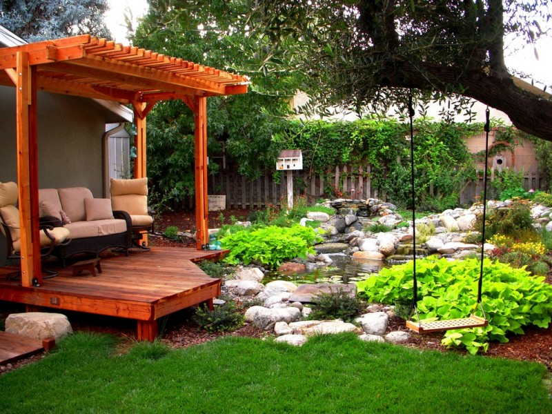 back yard pond grass fence chairs wood floor stones traditional landscape