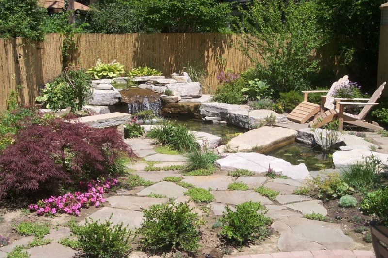 back yard pond seating stones fence flowers plants outdoor area contemporary landscape