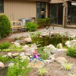 back yard pond seating window house exterior stones flowers traditional landscape