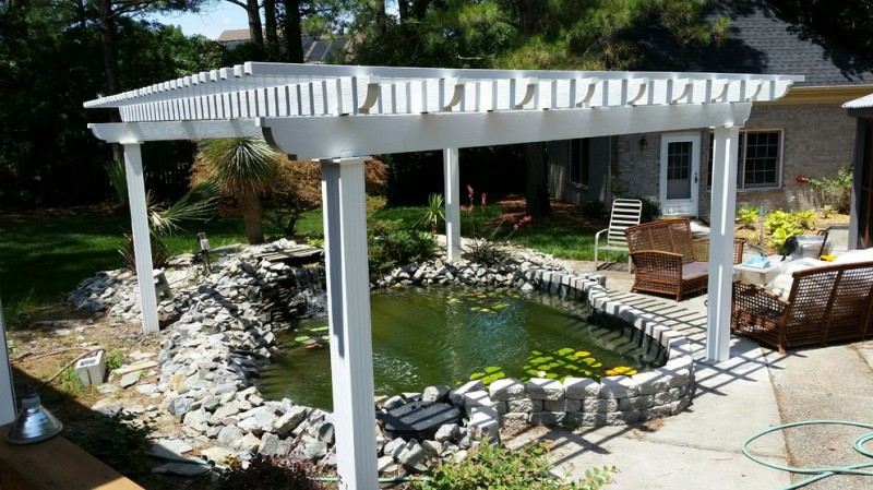 back yard pond window chair seating stones house exterior tropical landscape