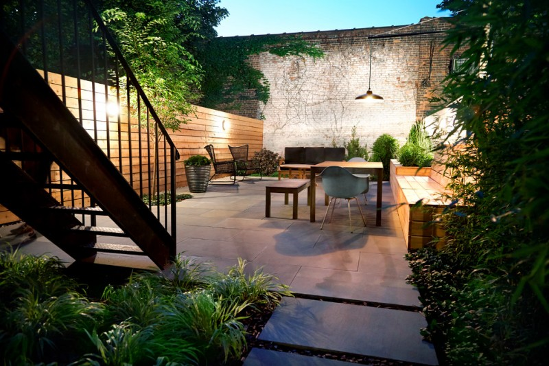 backyard patio design tables chairs bench lamps hanging lamp plants wall cool lighting contemporary outdoor area