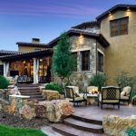 backyard patio designs chairs firepit rocks curtains windows lamps stairs plants flowers stone walls contemporary style