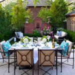 backyard patio designs chairs table pillows tree grass plants flowers traditional outdoor area