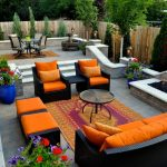 backyard patio designs firepit chairs tables fence oversized couch pillows flowers traditional style