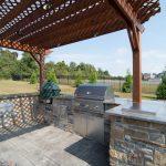 Backyard Patio With Custom Wood Pergola And Outdoor Kitchen Concrete Pavers Flooring Idea Veneer Stones Kitchen Counter With Granite Top