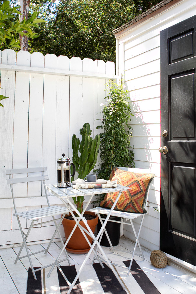 balcony with white wooden flooring, white high vertical wooden fence