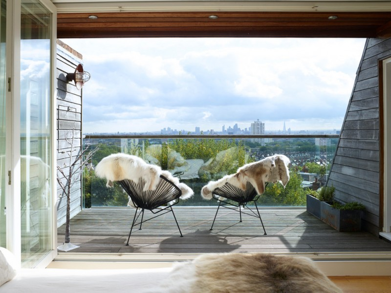 balcony with wooden flooring, high wooden horizontal wooden wall, glass rail, black metal frame chair