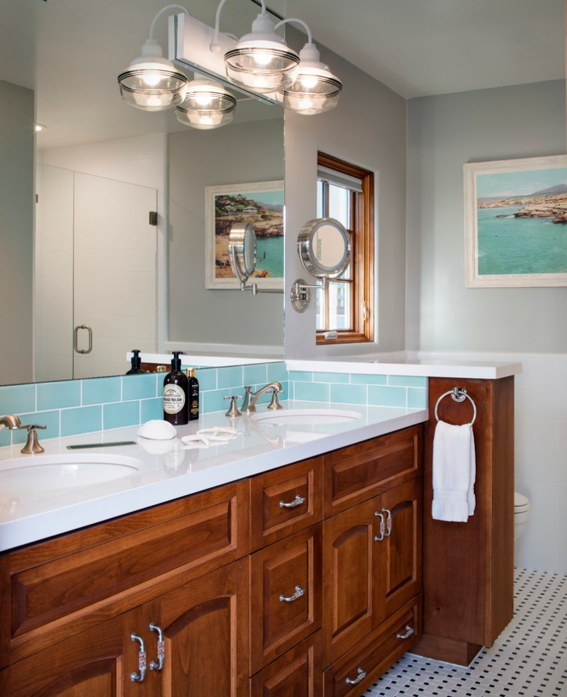 bathroom sink with dark wooden cabinet, white top, white sink, blue tiles for backsplash, large mirror, round towel bar, glass lamps