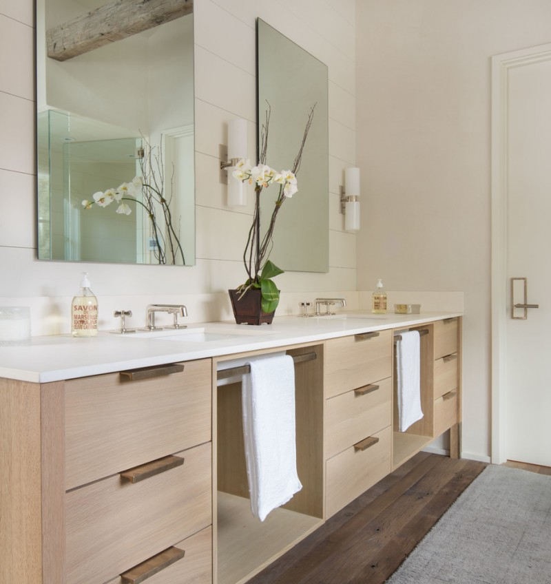 bathroom with double brown cabinet with towel bar, white top sink, mirrors
