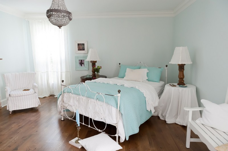 beach style bedding idea in white and blue white coverd bedside tables medium toned wood floors wooden base table lamps light blue walls white stripes armchair