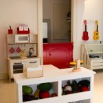 best play kitchens mini stove faucet sink oven island storage spaces white wall traditional kids room