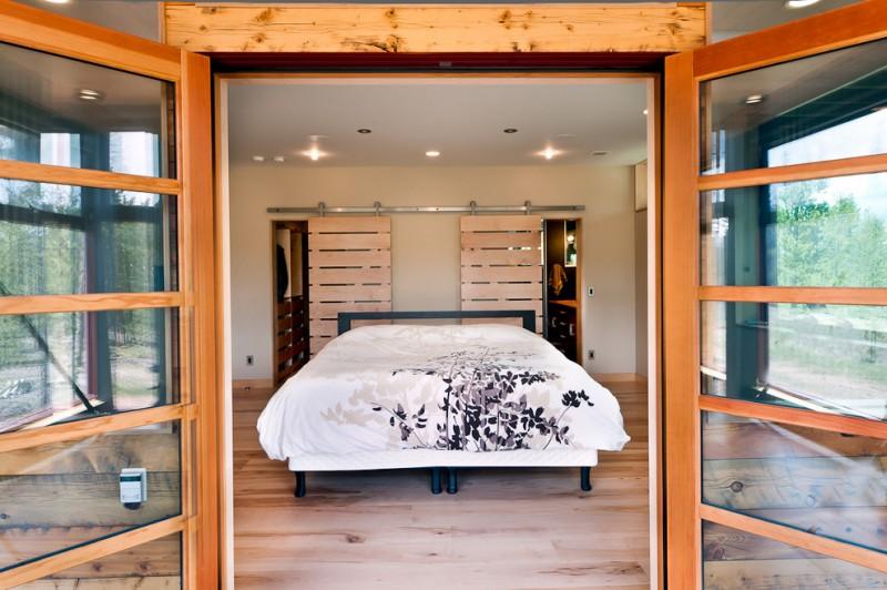 big walk in closet bed sliding doors ceiling lights wood floor floral patterns modern bedroom