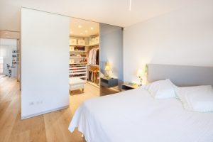 big walk in closet light coloured floor bed pillows clothes ceiling lights cool lamp shelves contemporary bedroom