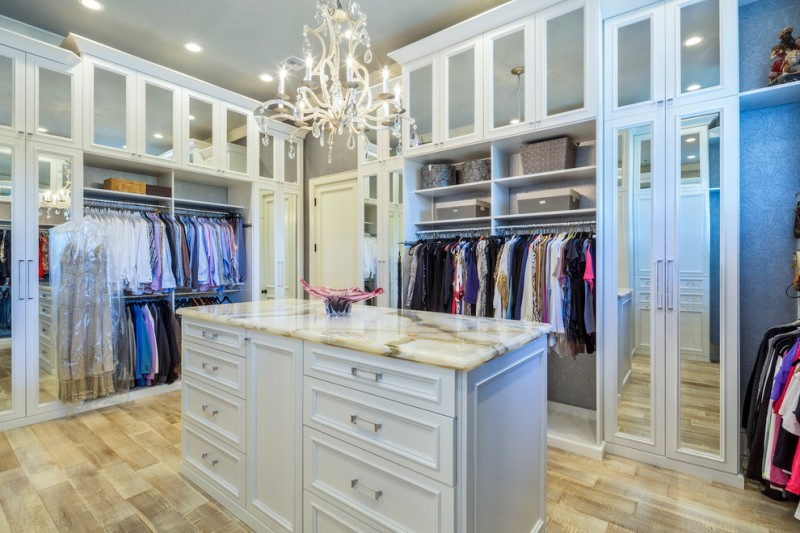 big walk in closet light coloured floor clothes chandelier shelves drawers ceiling lights traditional bedroom