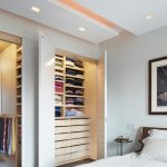 big walk in closet wood floor bed clothes pillows shelves small bedside table contemporary bedroom