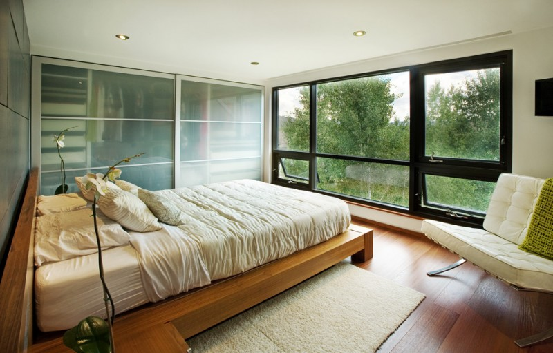 big walk in closet wood floor bed pillows big windows flowers modern bedroom
