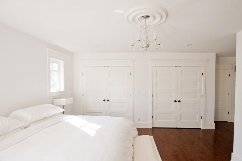 big walk in closet wood floor bed pillows small window chandelier beach style bedroom